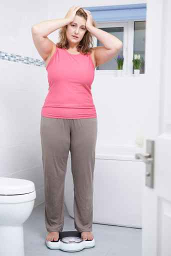 unhappy woman on scale after binge eating