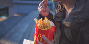 emotional eating, a man eating fries, fried food, unhealthy, payoff